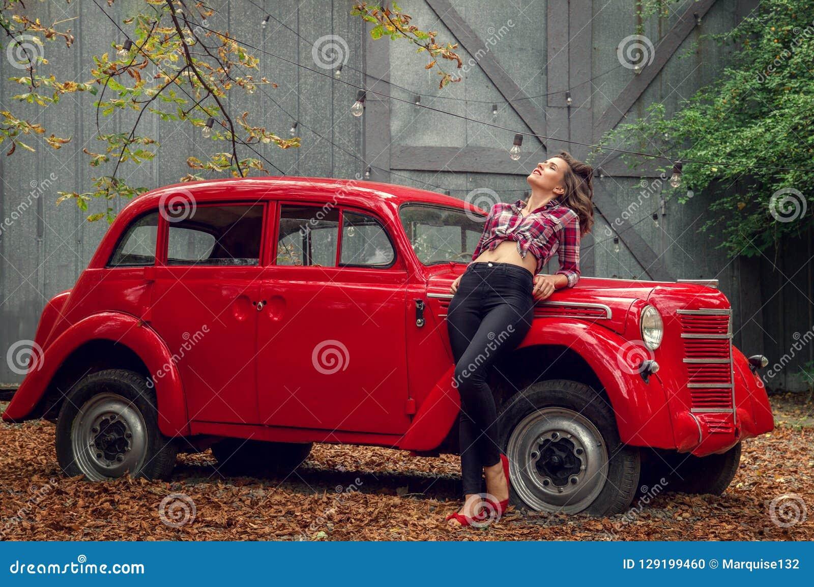 La muchacha Pin-para arriba en vaqueros y una camisa de tela escocesa se está inclinando en un coche retro rojo ruso