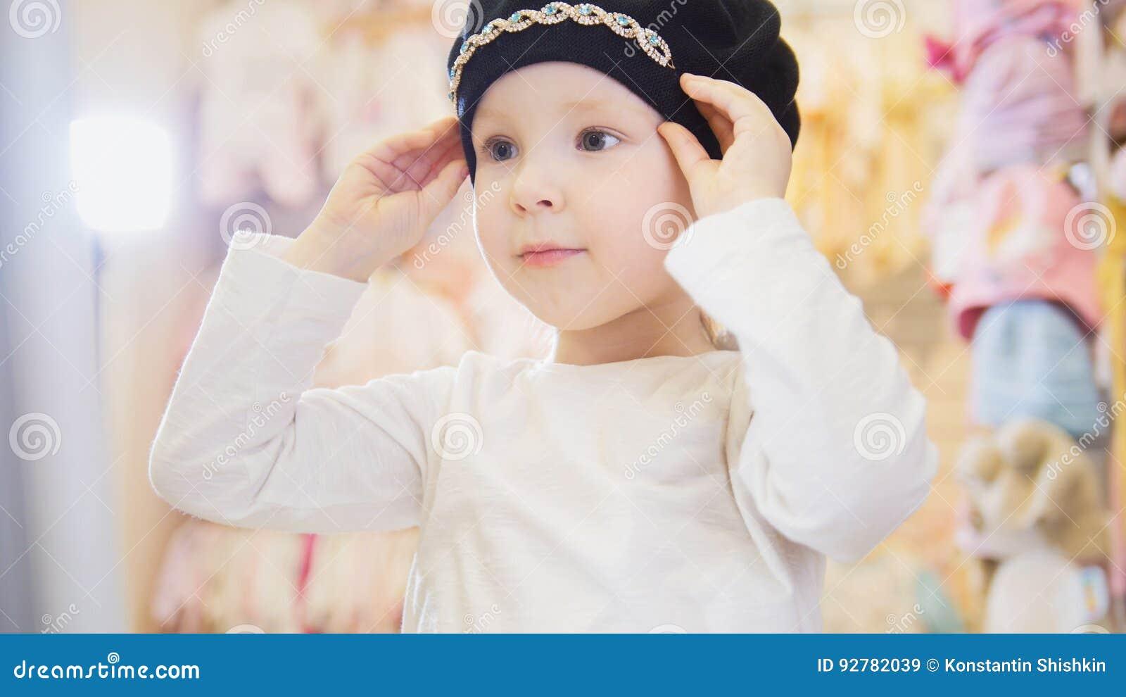 La muchacha preciosa intenta encendido una boina negra delante de un espejo  en una tienda de ropa para los niños 8a9ae97d242
