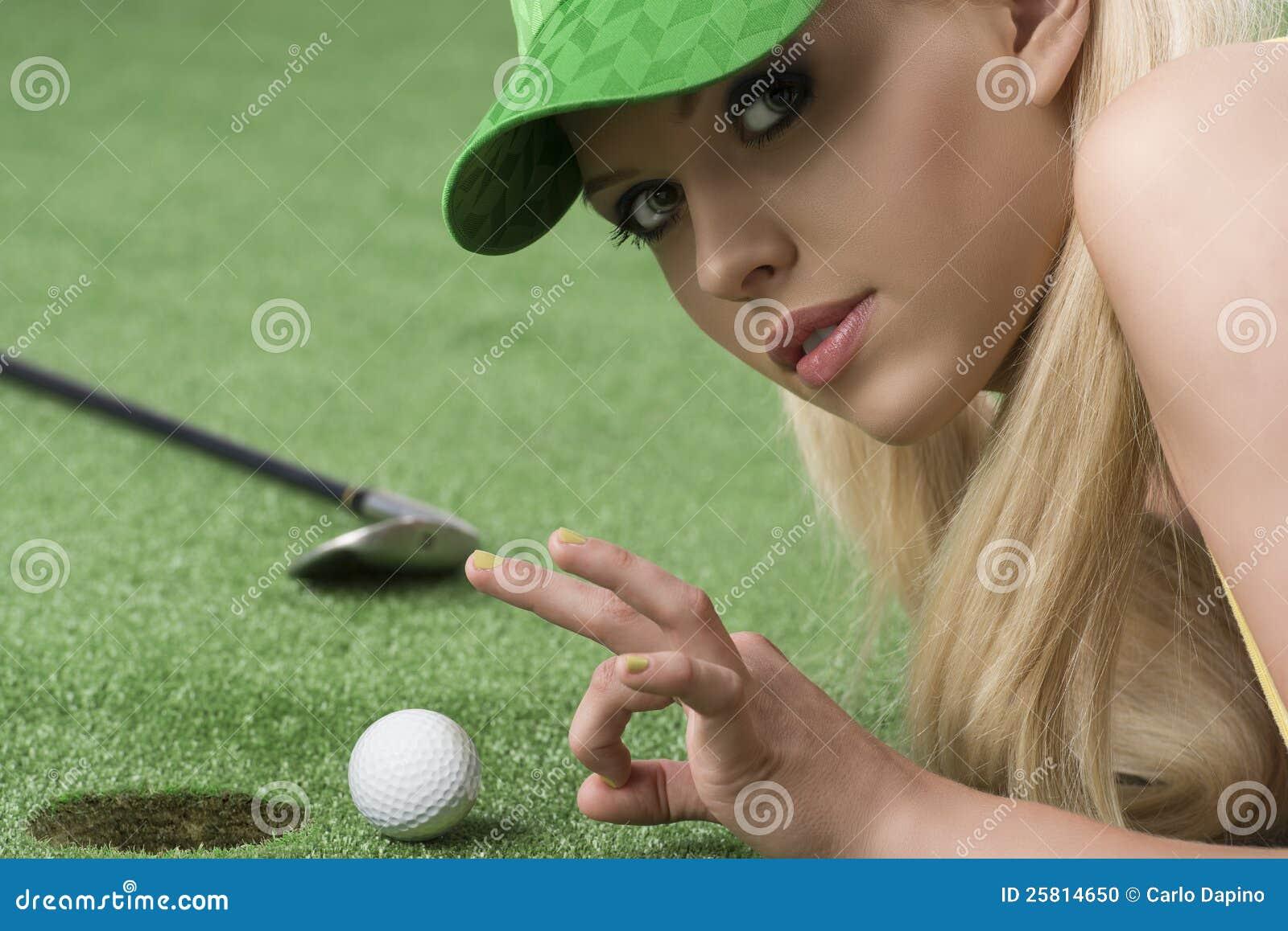 La muchacha que juega con la pelota de golf mira adentro a la lente