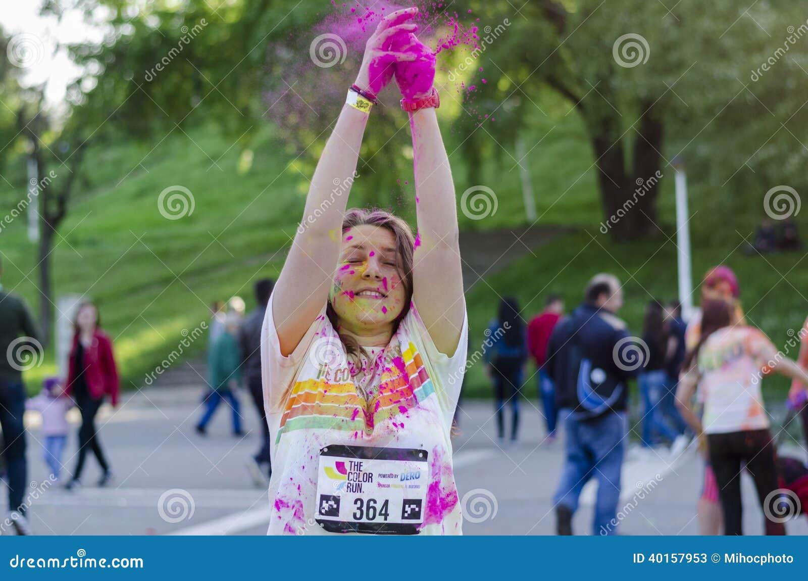 La muchacha que lanza el polvo rosado en el color corre Bucarest