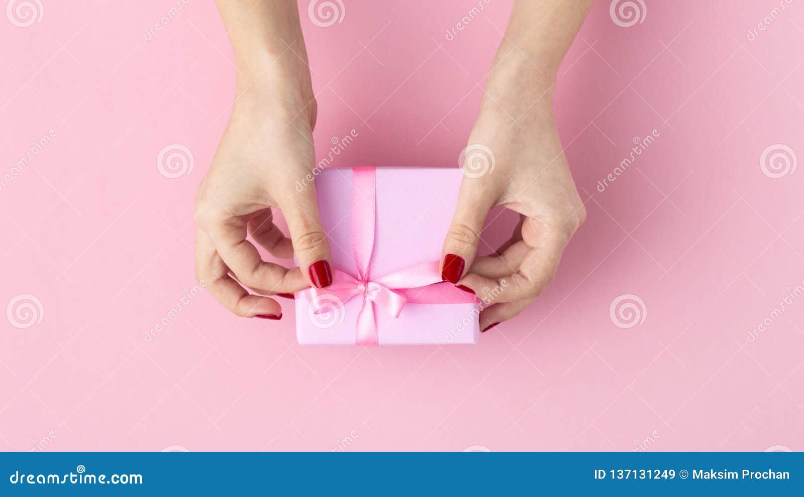 La muchacha que lleva a cabo un presente en las manos, las manos de las mujeres abre la caja envuelta en el documento decorativo