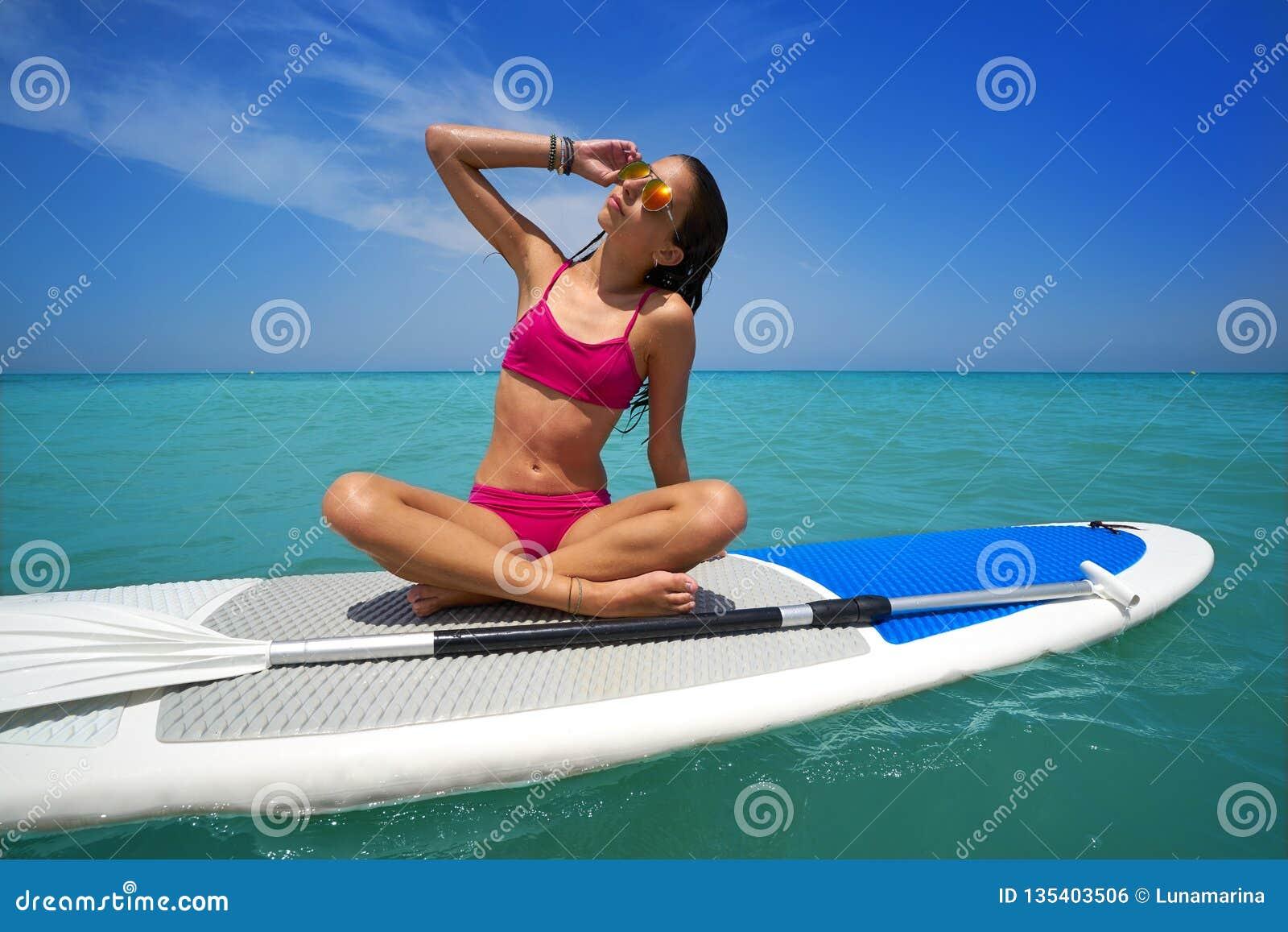 La muchacha relajó sentarse en SORBO del tablero de resaca de la paleta