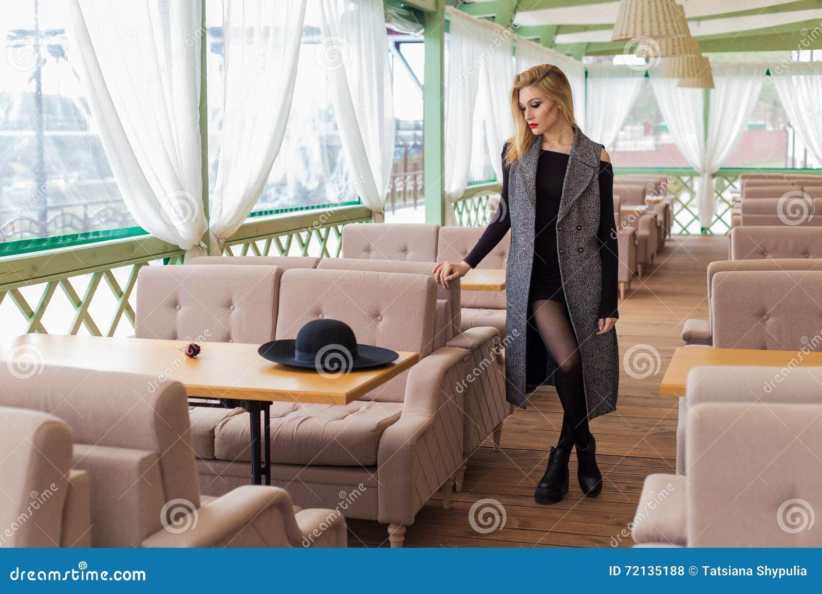 La muchacha rubia atractiva atractiva hermosa en un café en un sombrero negro y capa con smokey de moda del maquillaje observa