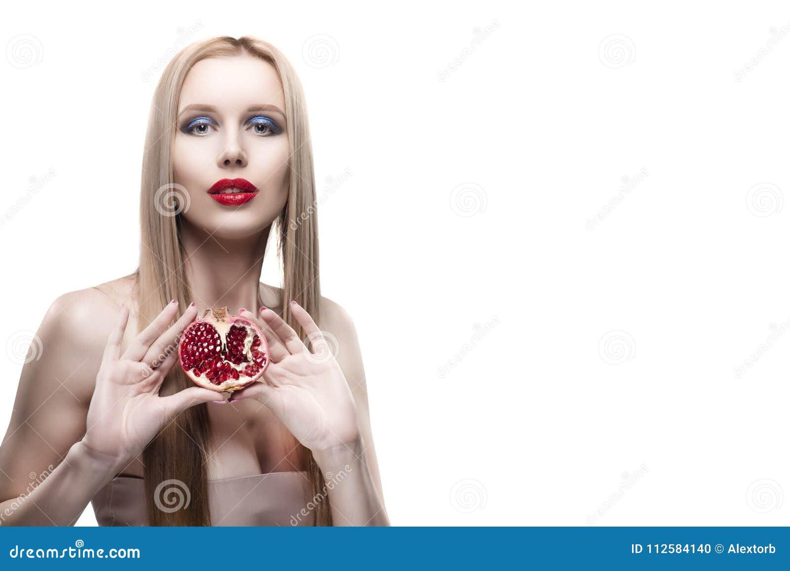La muchacha rubia de los labios rojos de pelo largo jovenes hermosos lleva a cabo una mitad de