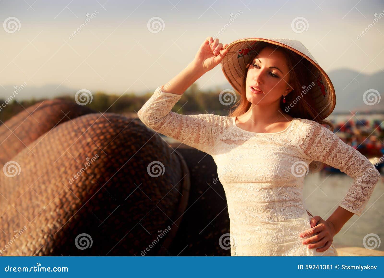 La muchacha rubia en el vestido blanco toca sonrisas del sombrero en la barrera