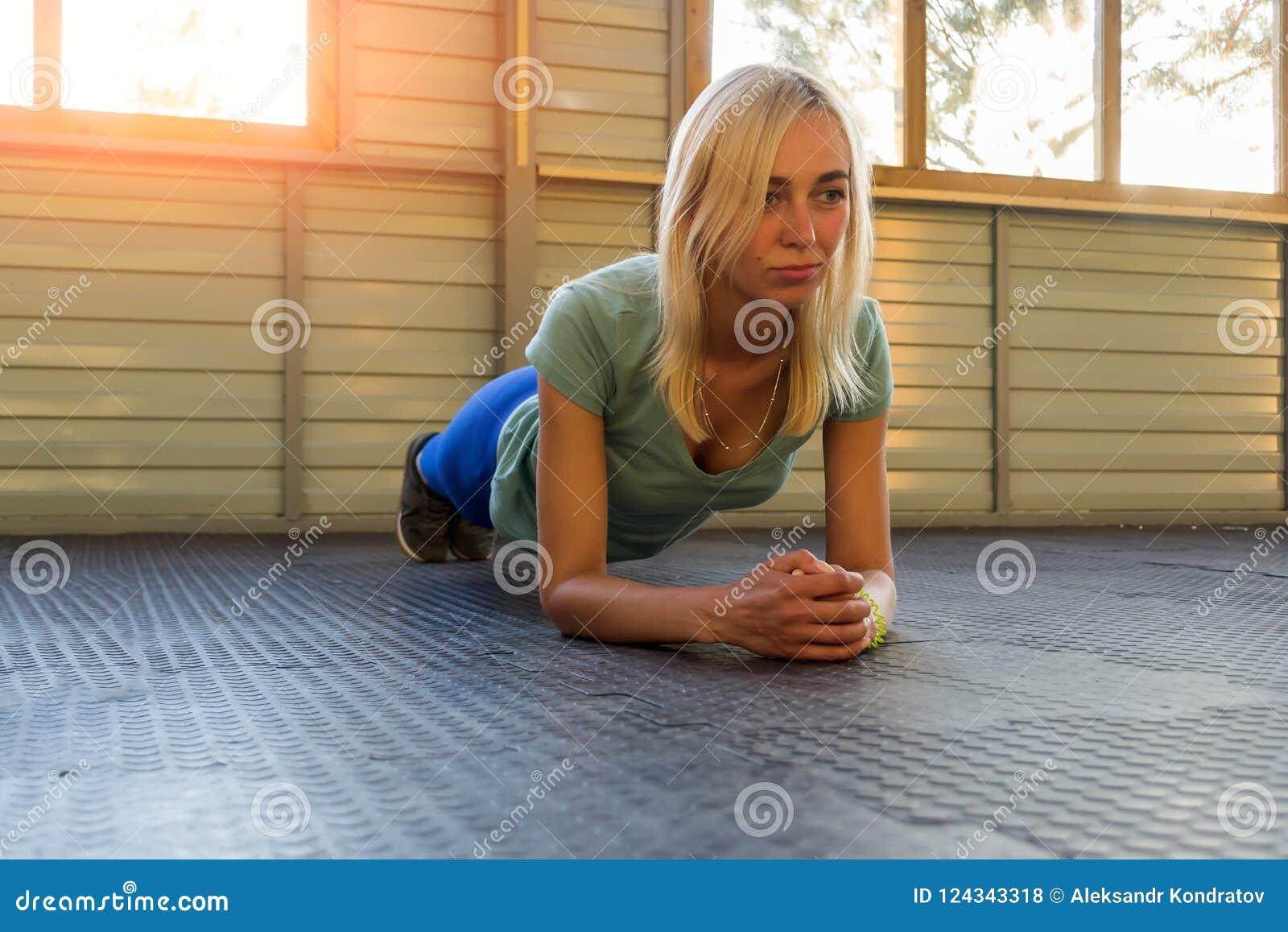 La muchacha rubia entrena en una capa de goma en el fondo de