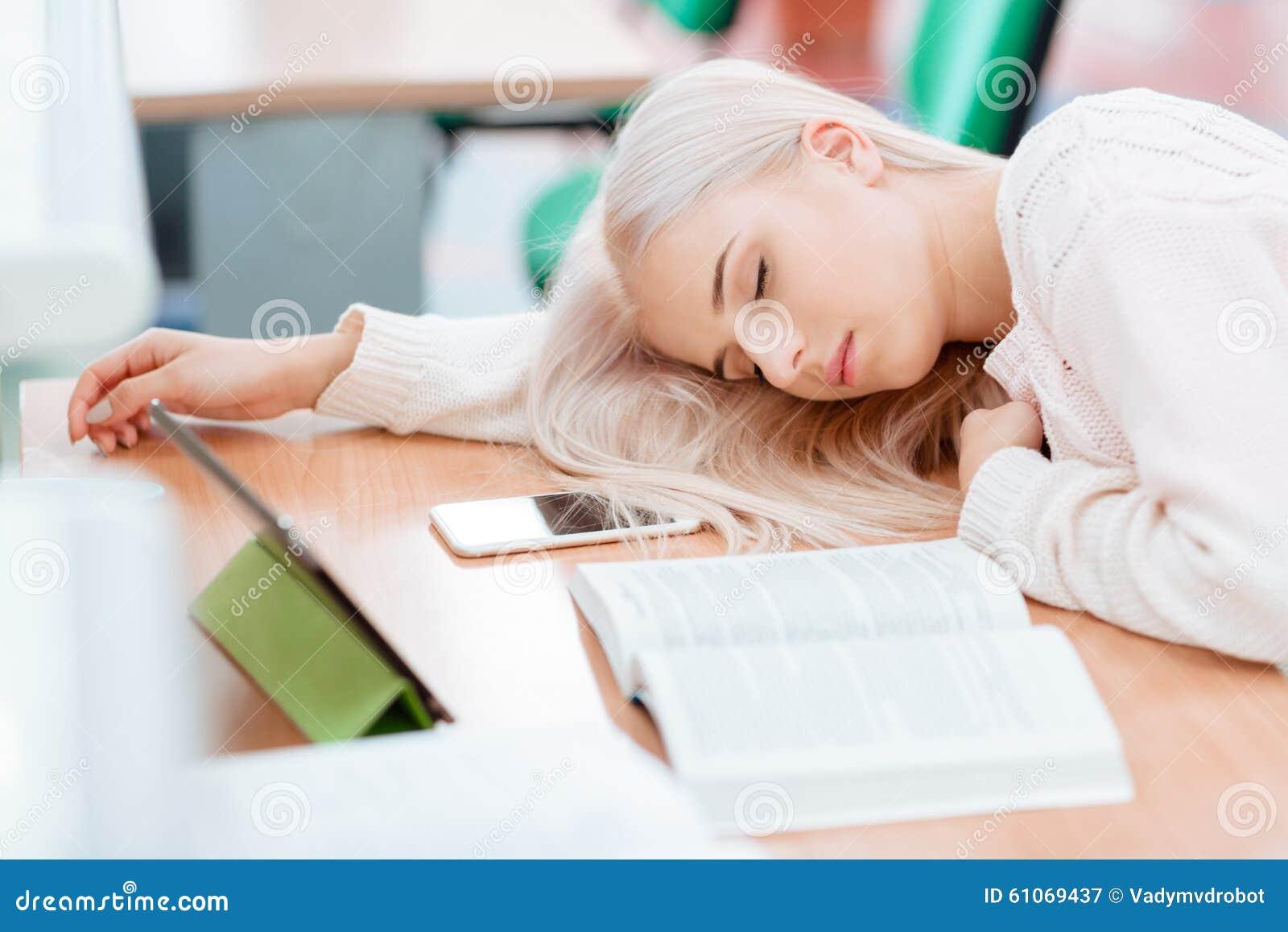 La muchacha rubia está durmiendo en el escritorio