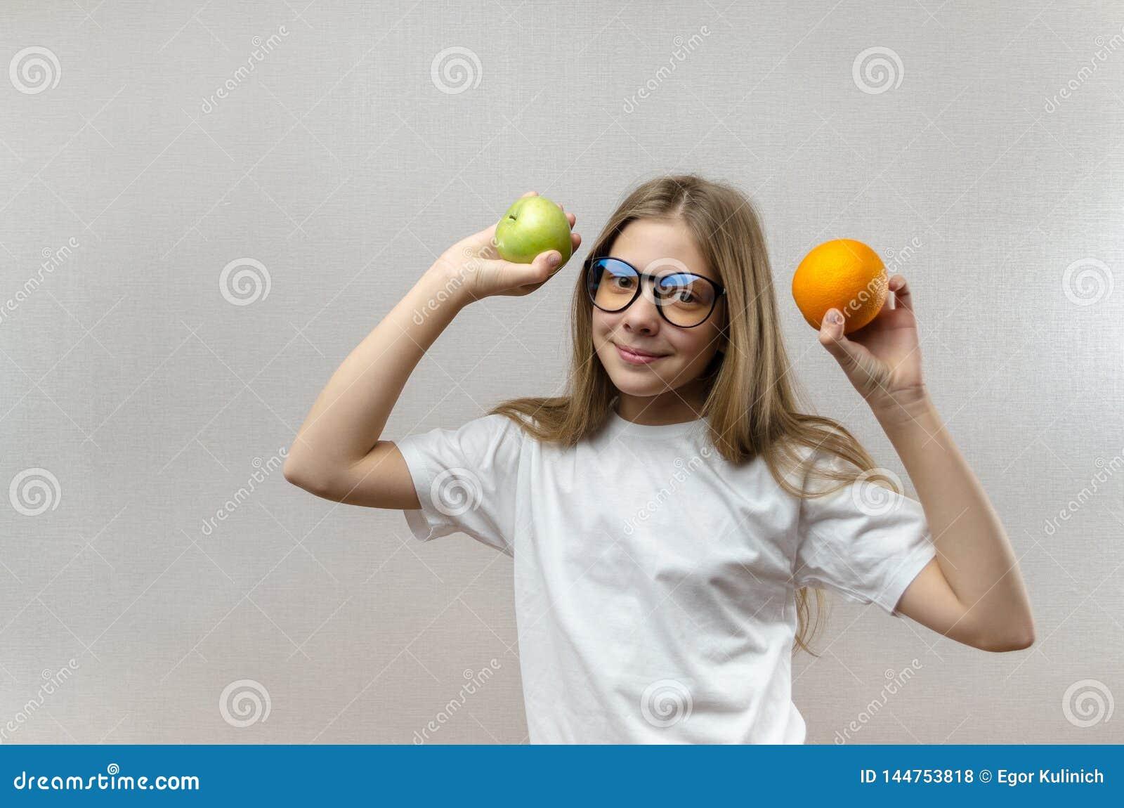 La muchacha rubia hermosa en una camiseta blanca sonr?e y sostiene una manzana y una naranja en sus manos Nutrici?n sana para