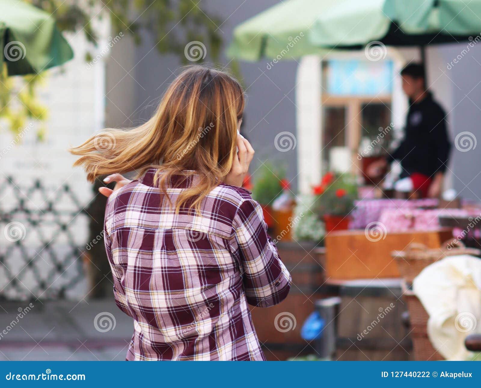 La muchacha rubia hermosa joven comunica en un smartphone en la calle de la ciudad vieja Artilugios en la comunicación diaria nue
