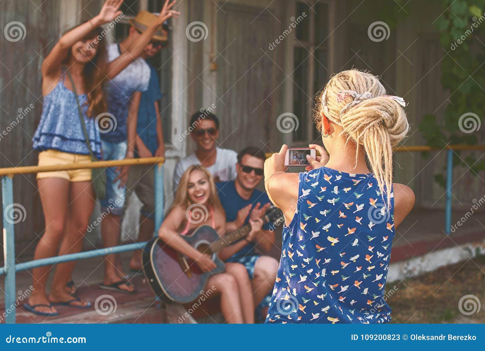 La muchacha rubia joven con teme toma una foto de grupos de sus amigos con su smartphone cerca de la cabina de madera del día de