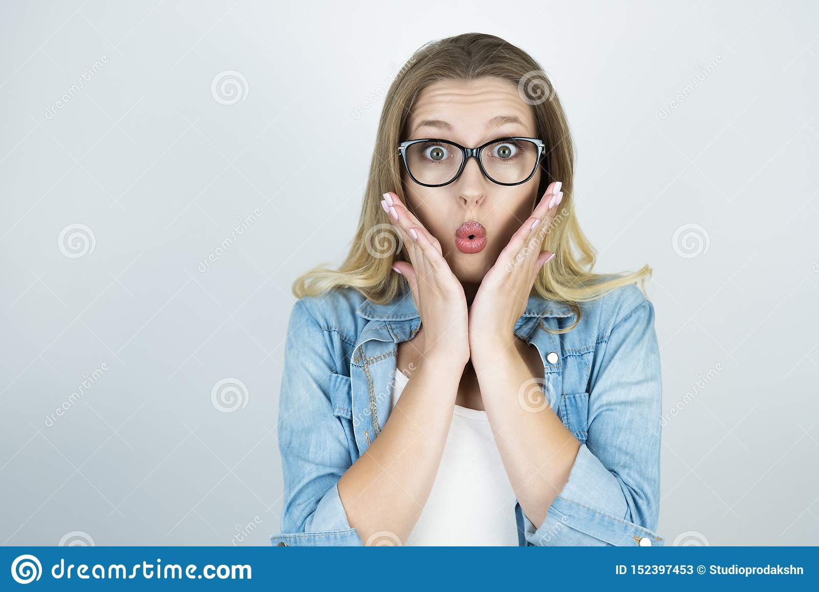 La muchacha rubia que llevaba a cabo las manos sorprendidas cerca de cara aisló el fondo blanco