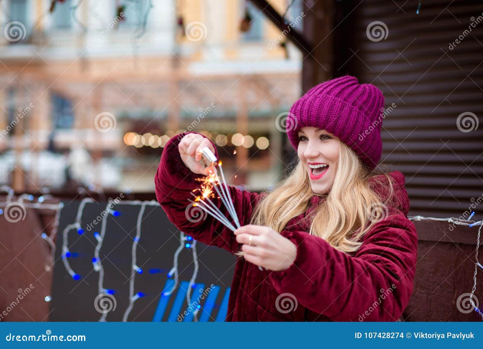 La muchacha rubia sorprendida se vistió en ropa elegante, fija el fuego al gl