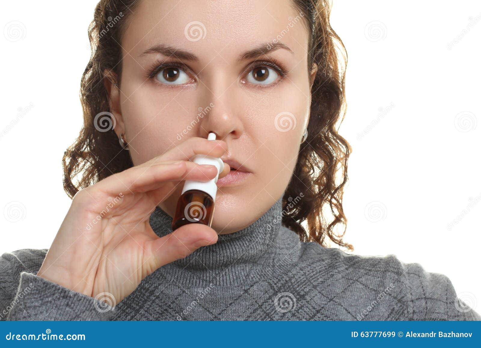 La muchacha salpica el espray en la nariz