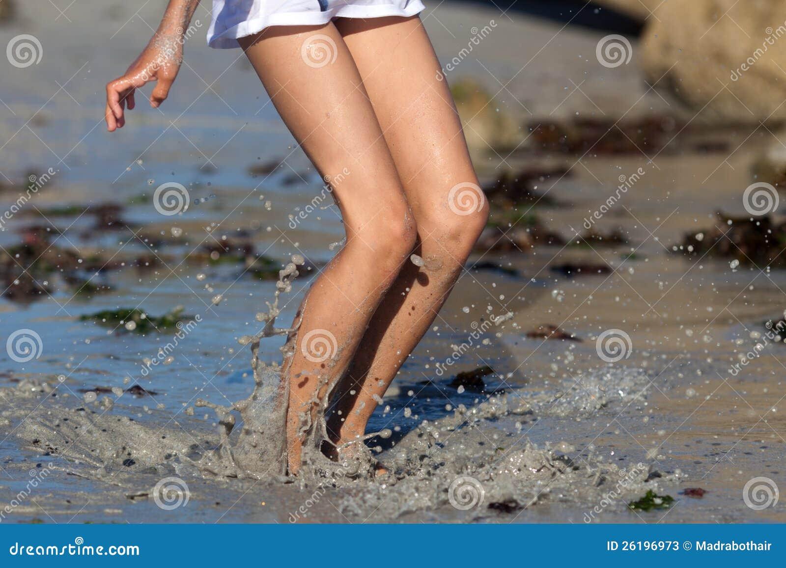 La muchacha salta en agua fangosa