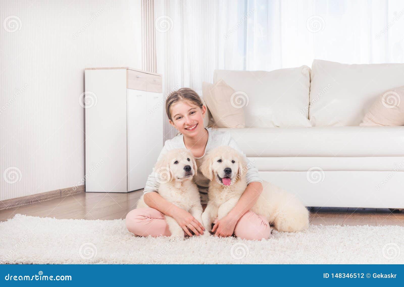 La muchacha se sienta abrazando perritos del perro perdiguero
