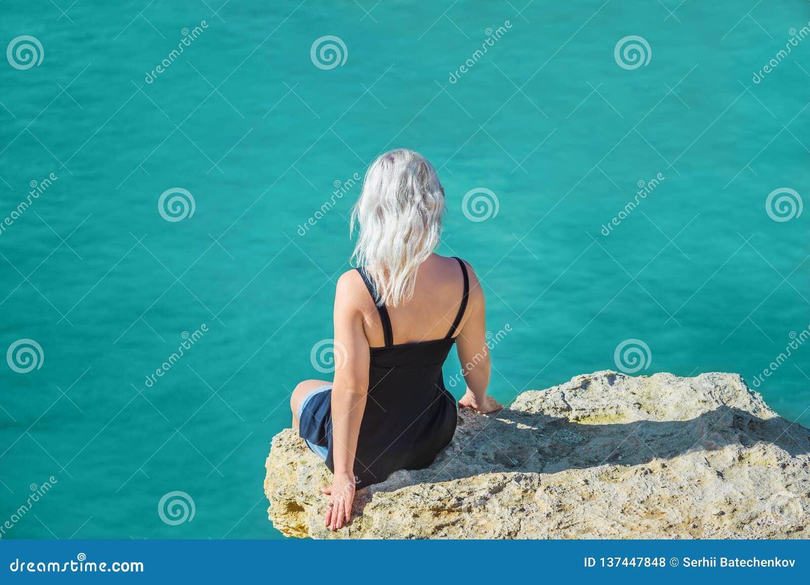 La muchacha se sienta en un acantilado sobre el océano