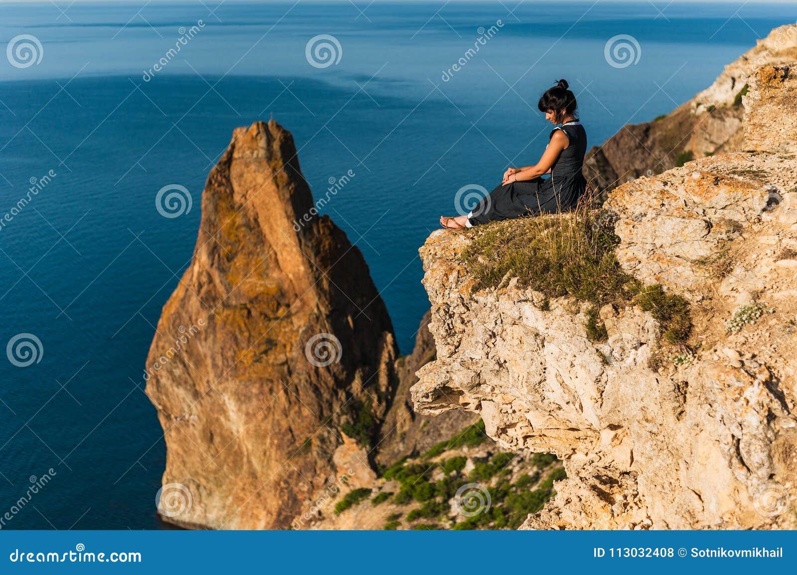La muchacha se sienta en una alta roca y mira el mar