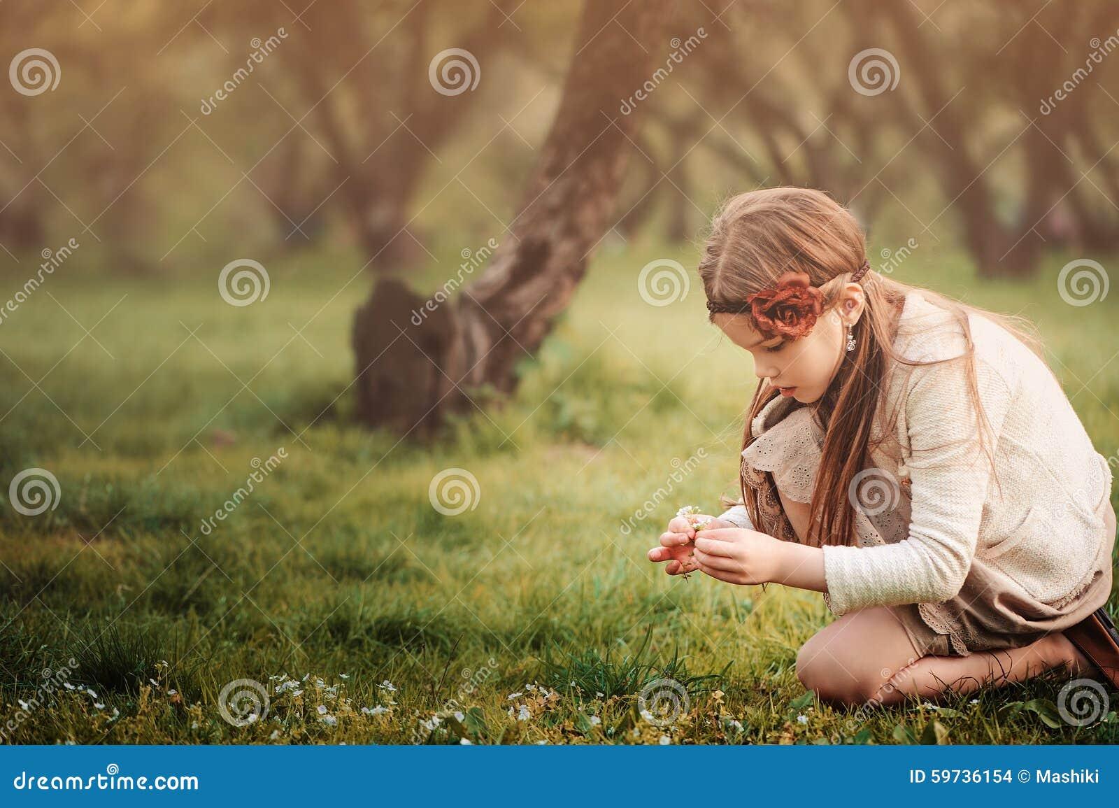 La muchacha soñadora linda del niño en la cosecha beige del equipo florece en jardín de la primavera