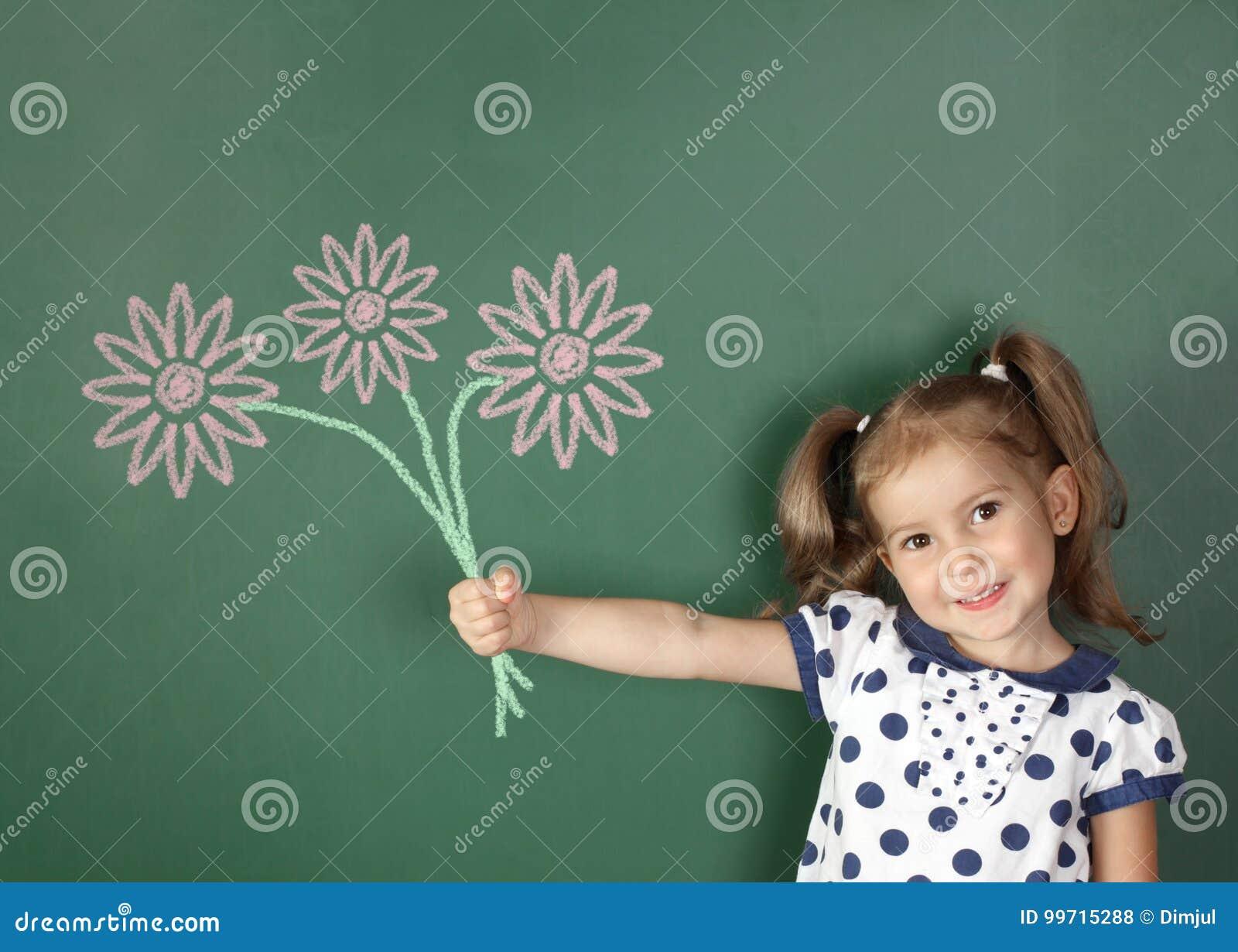 La muchacha sonriente del niño sostiene las flores exhaustas cerca de la pizarra de la escuela