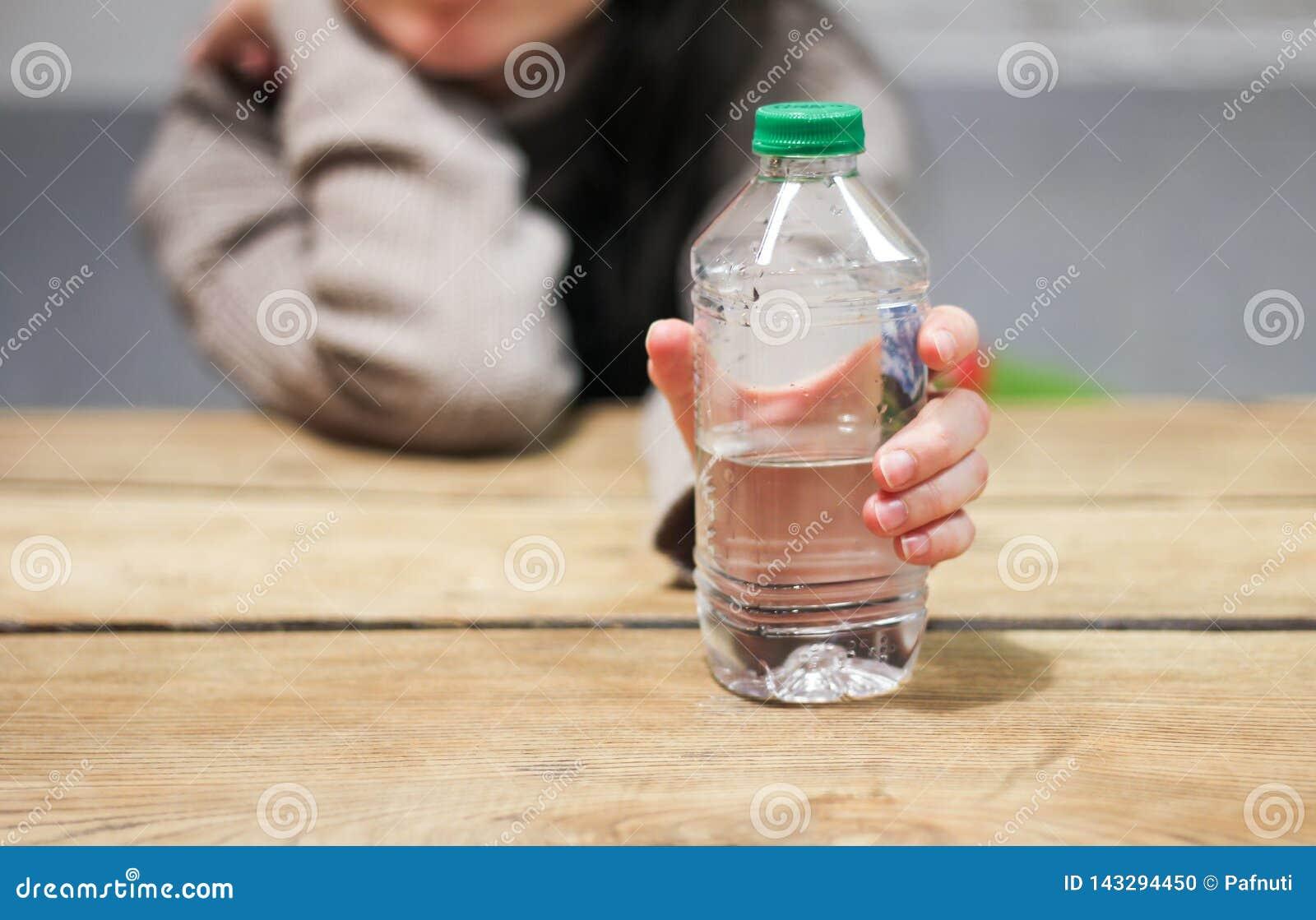 La muchacha sostiene en su mano una botella de agua en la tabla