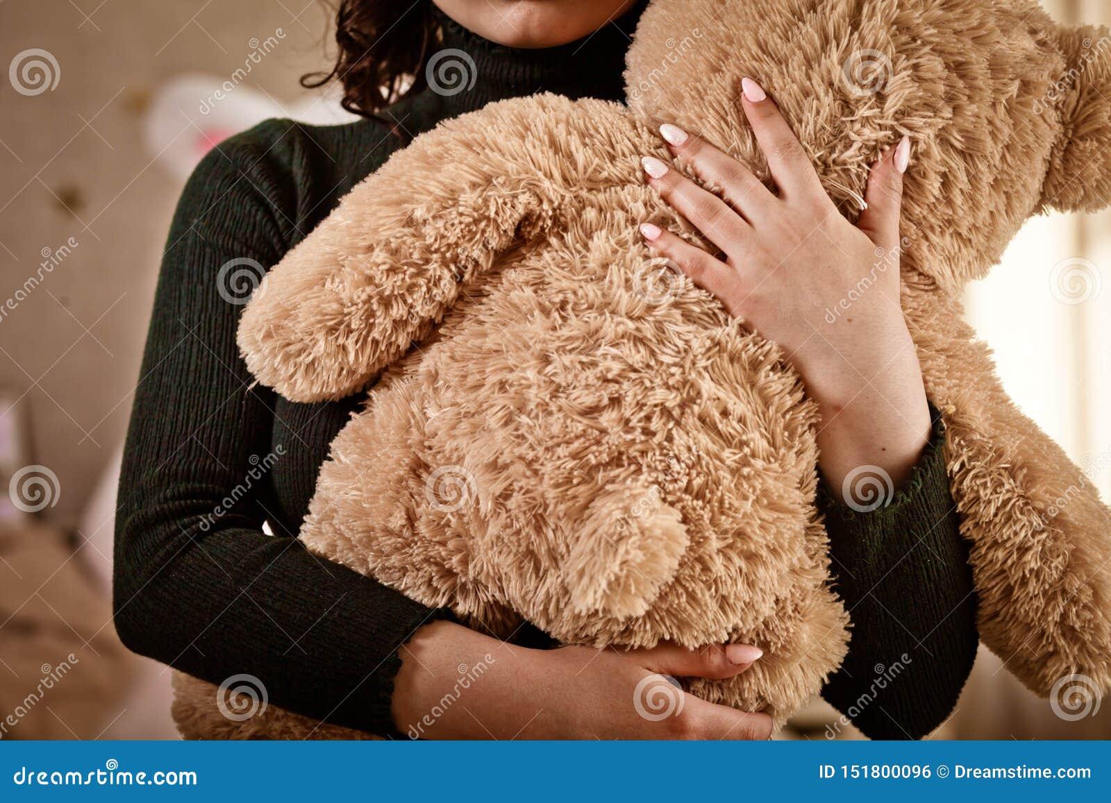 La muchacha sostiene un oso de un peluche, peluche