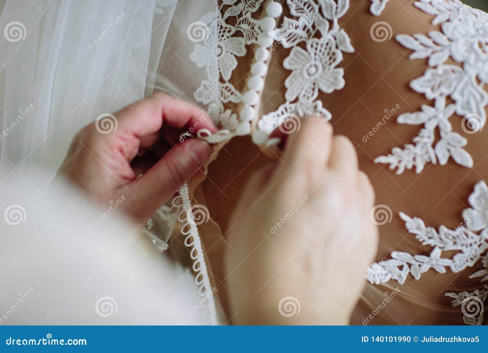 La muchacha sujeta el vestido de boda en la parte de atrás de la novia Cierre para arriba