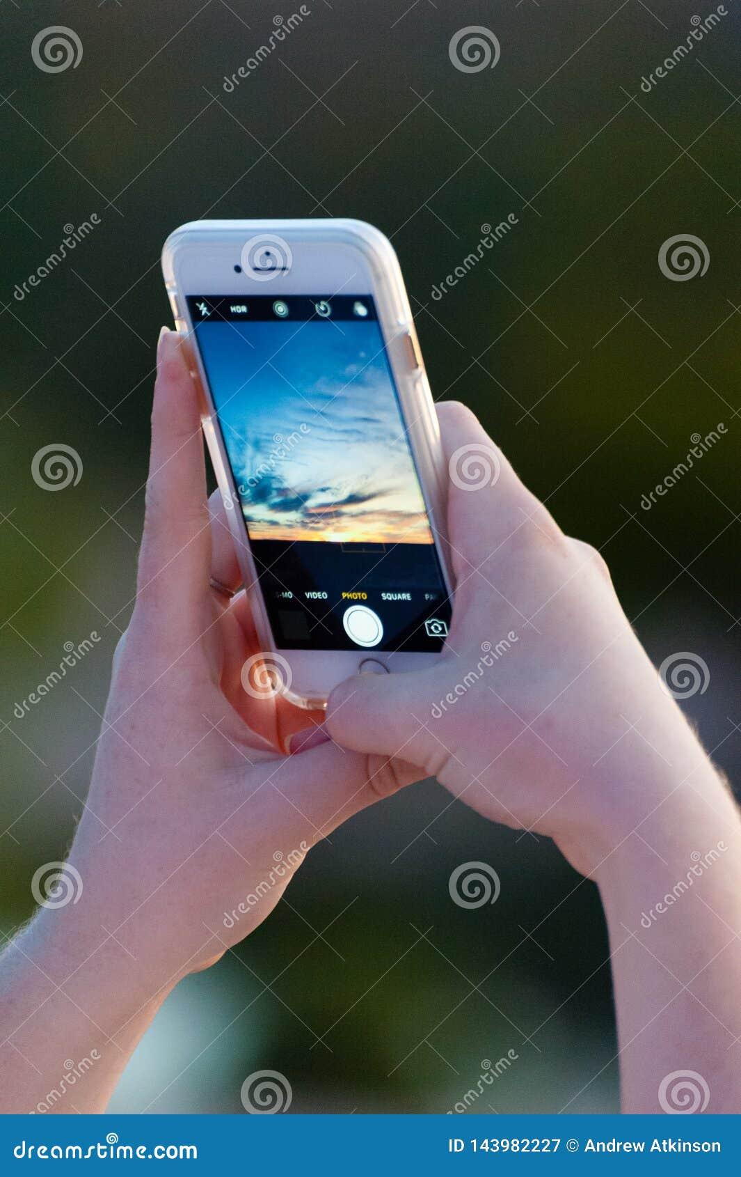 La muchacha toma una foto de una puesta del sol colorida hermosa en su teléfono