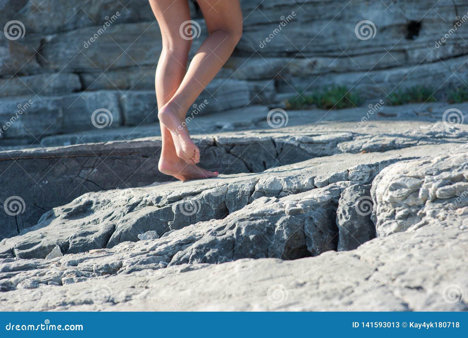 La muchacha va descalzo en las rocas, subiendo para arriba