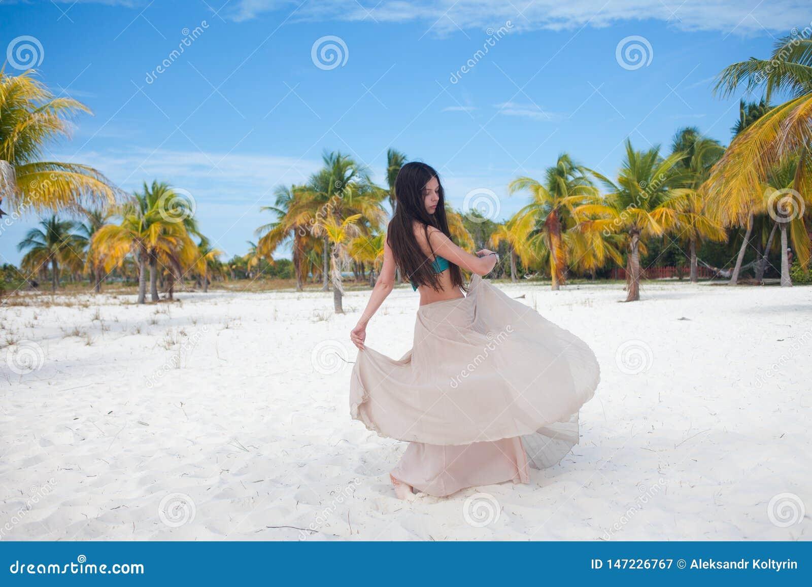 La muchacha viaja al mar y es feliz Baile moreno atractivo joven de la mujer que agita su falda contra paisaje tropical