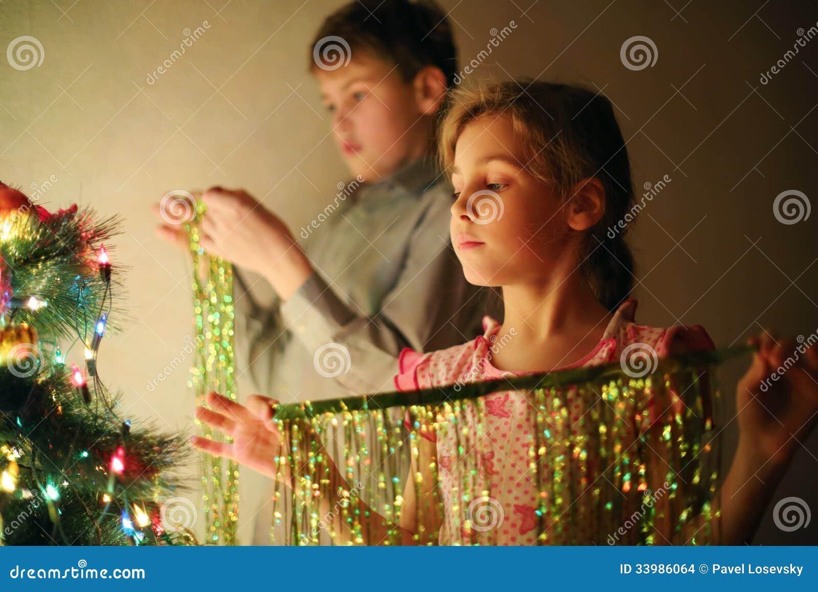 La muchacha y el muchacho adornaron el árbol de navidad con malla en la tarde