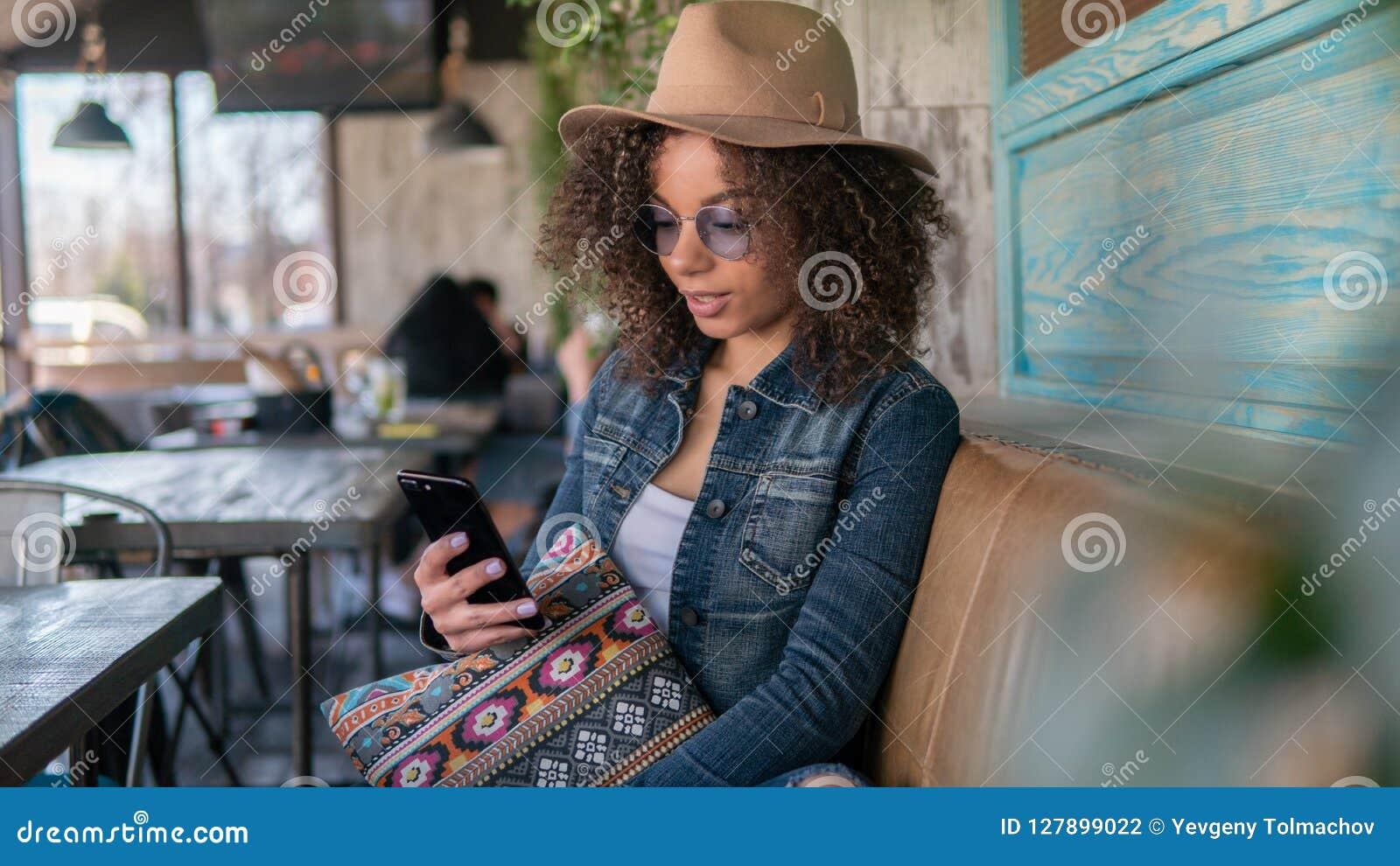 La mujer afroamericana charla el café en línea, interior