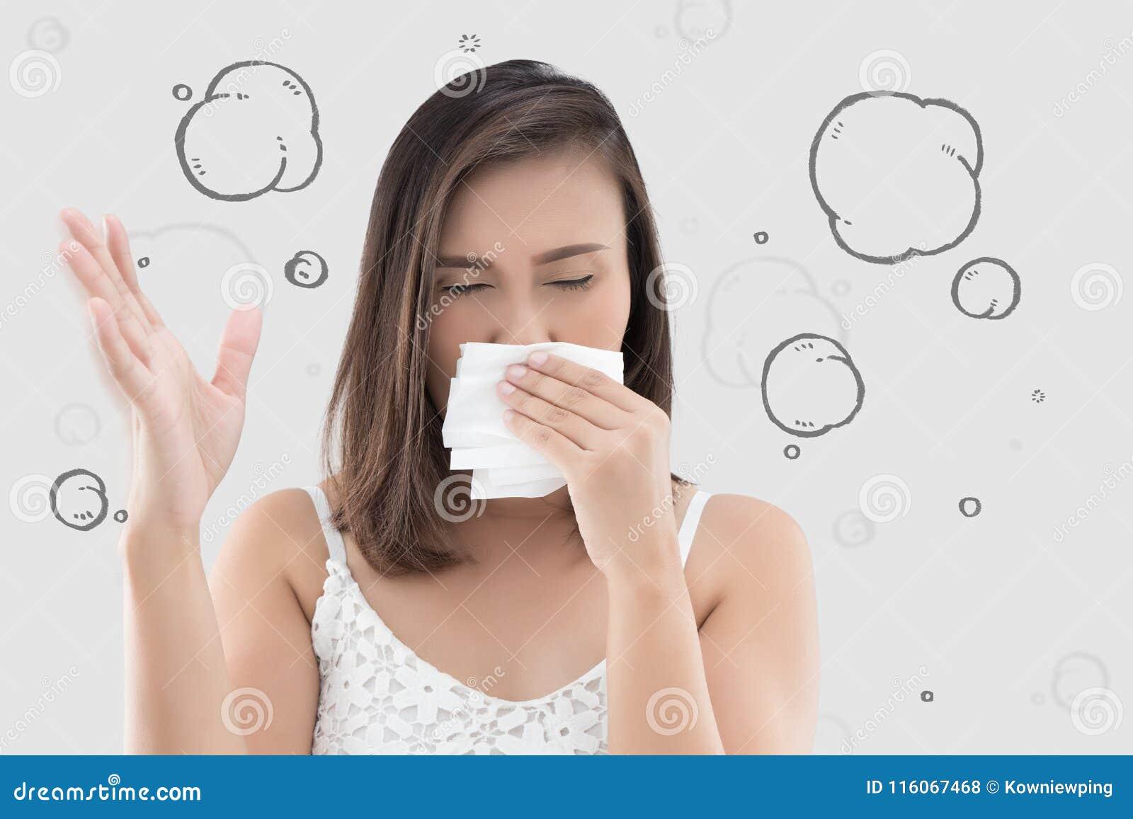 La mujer asiática en el vestido blanco coge su nariz debido a un mún olor