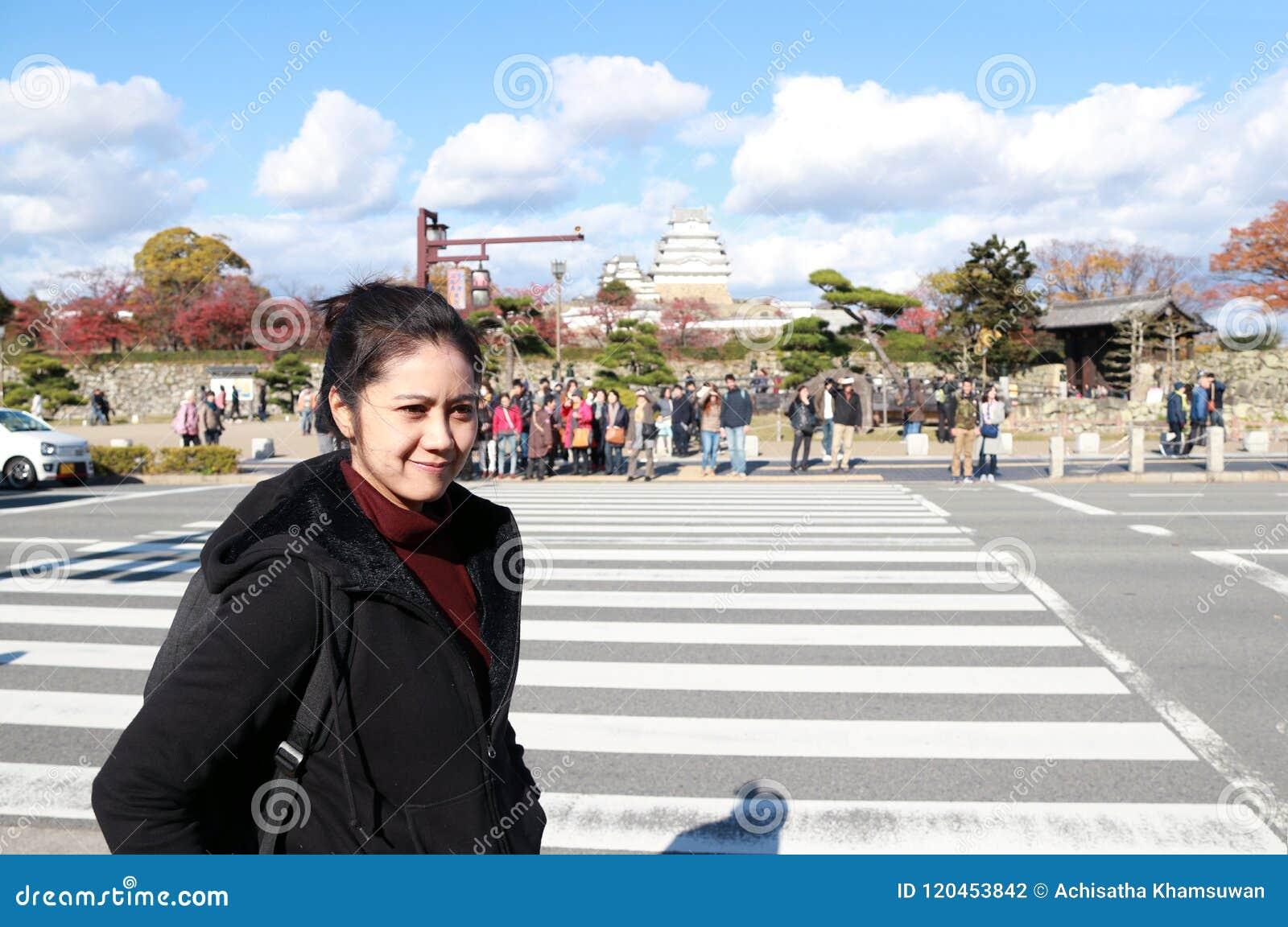 La mujer asiática en la ropa negra que se coloca al lado del camino y el paso de peatones con hacia fuera enfocan al turista