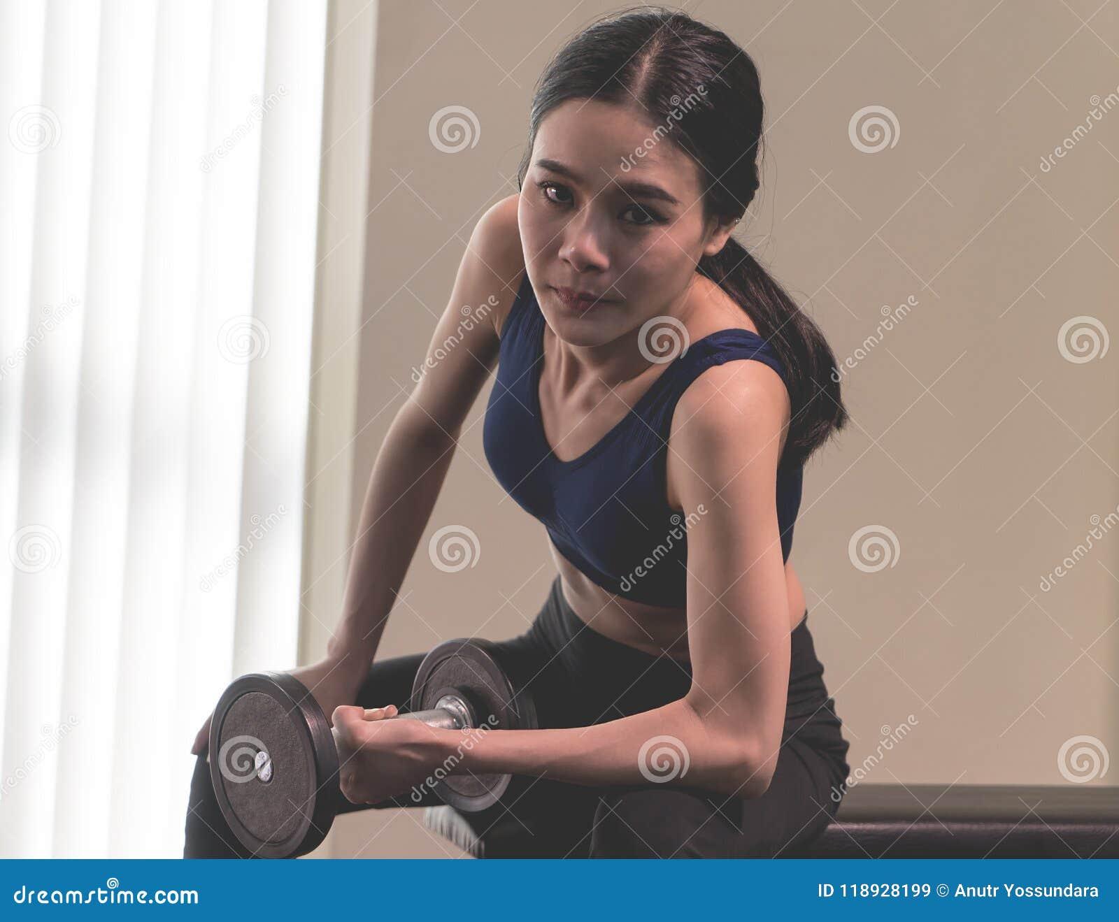 La mujer asiática fuerte está levantando pesa de gimnasia en aptitud