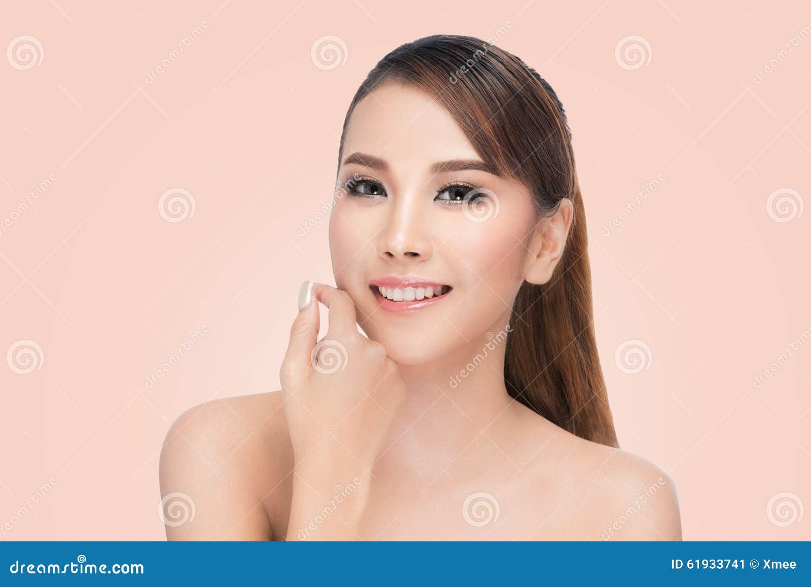 La mujer asiática hermosa cuida para el balneario hermoso de la cara de la piel