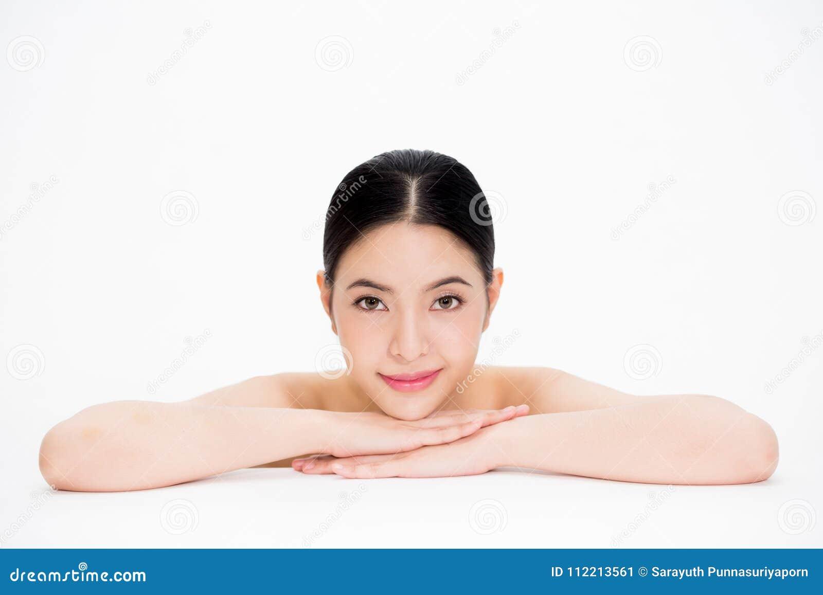 La mujer asiática hermosa joven con el skincare liso y perfecto en blanco aisló el fondo
