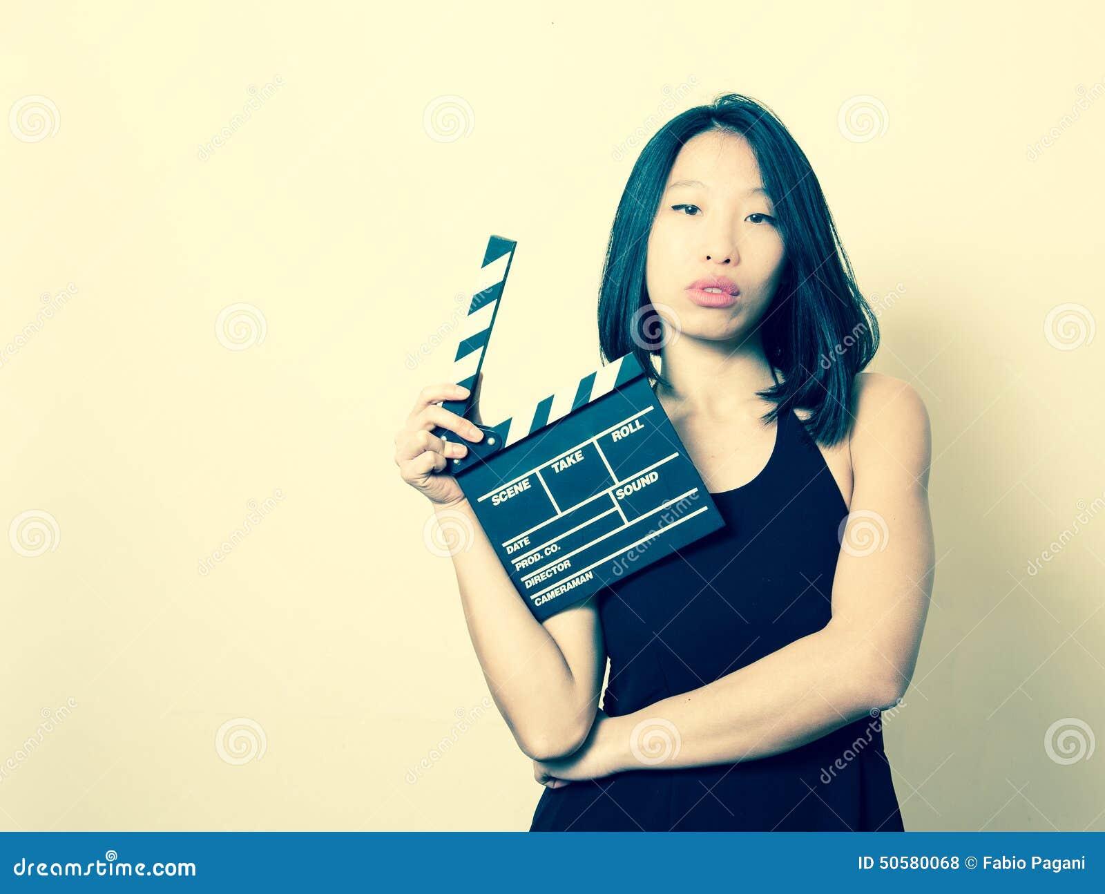 La mujer asiática hermosa joven con el vintage del clapperboard colorea por