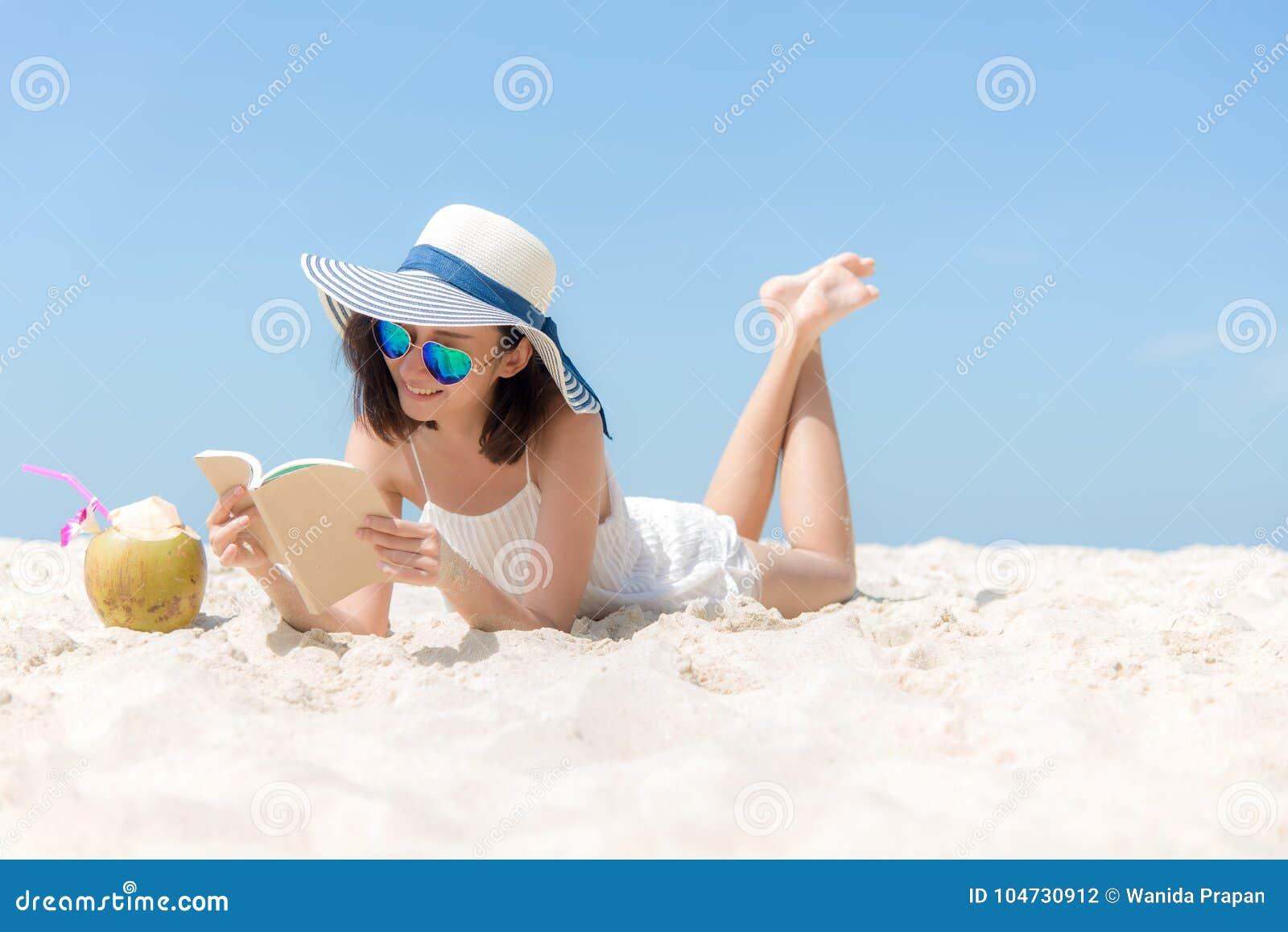 La mujer asiática joven de la forma de vida se relaja y leyendo un libro en la playa hermosa el verano del día de fiesta,