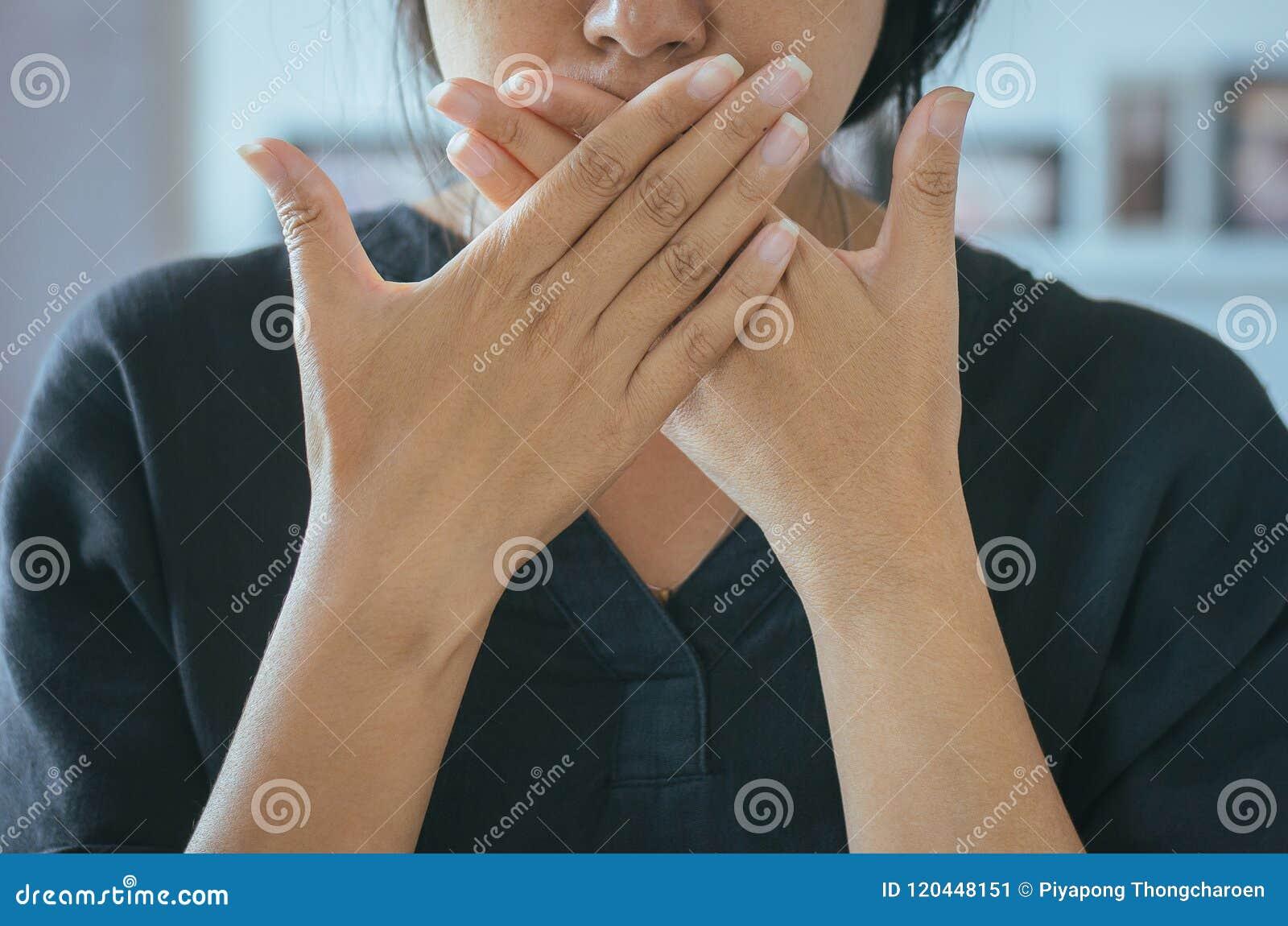 La mujer asiática que cubre su boca y huele su respiración con las manos que el upter despierta, mún olor