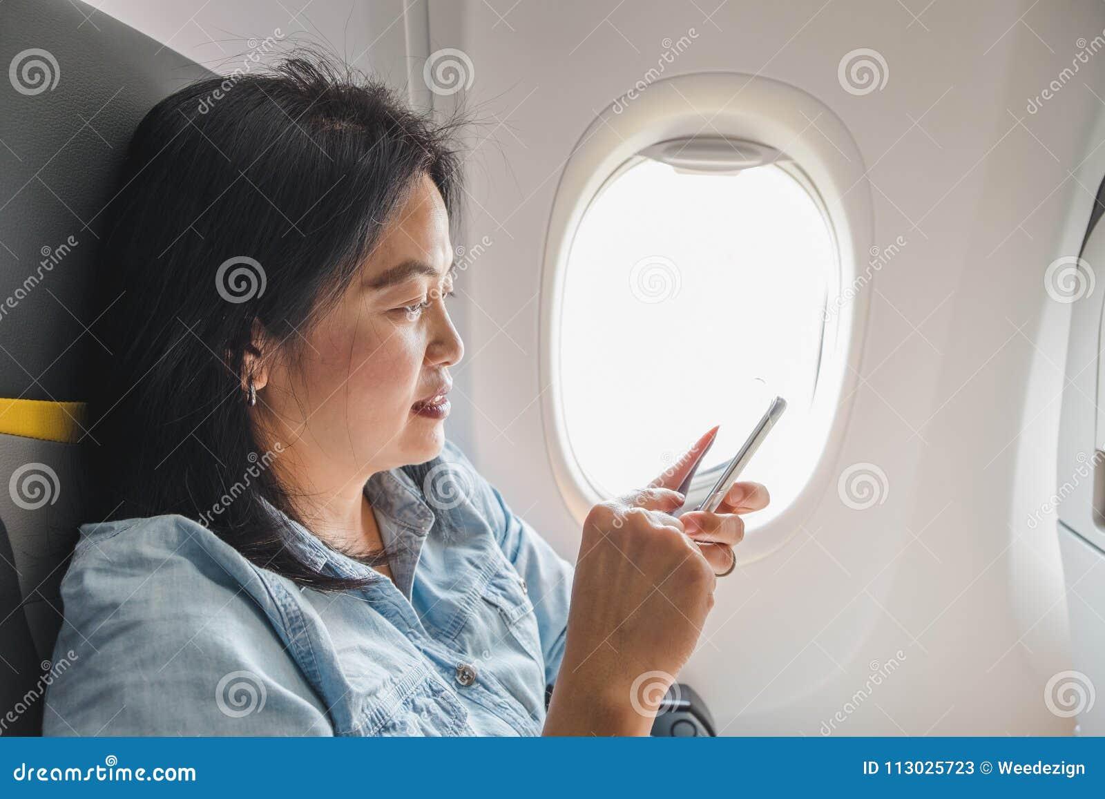 La mujer asiática que se sienta en el asiento de ventana en aeroplano y gira el airpl