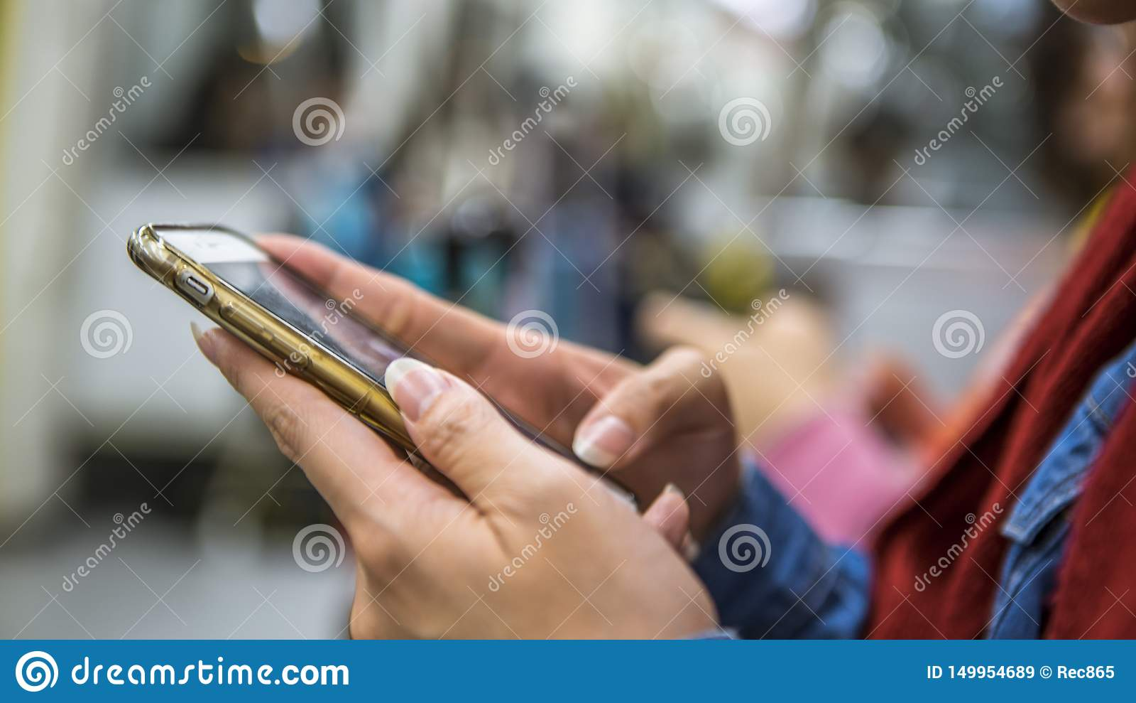 La mujer asiática se sienta en smartphone del metro y de los controles Pasajero que usa el teléfono
