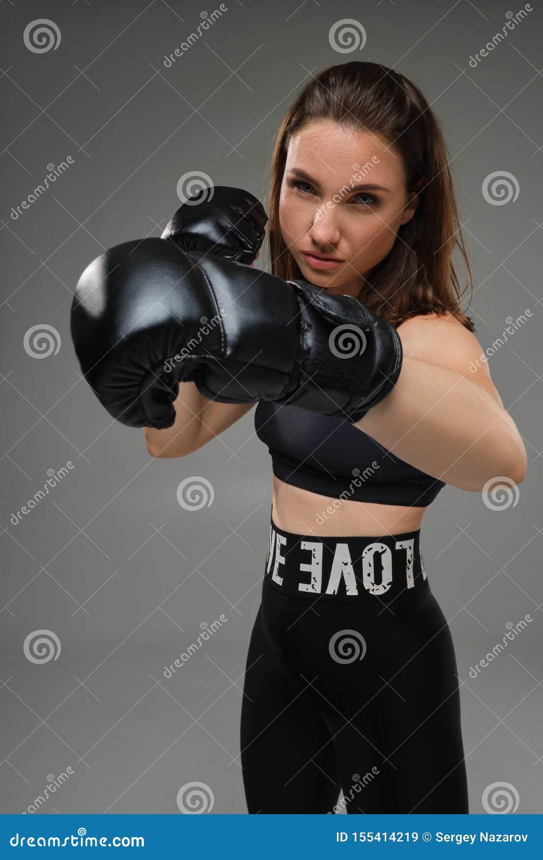 La mujer atlética en guantes de boxeo está practicando karate en estudio