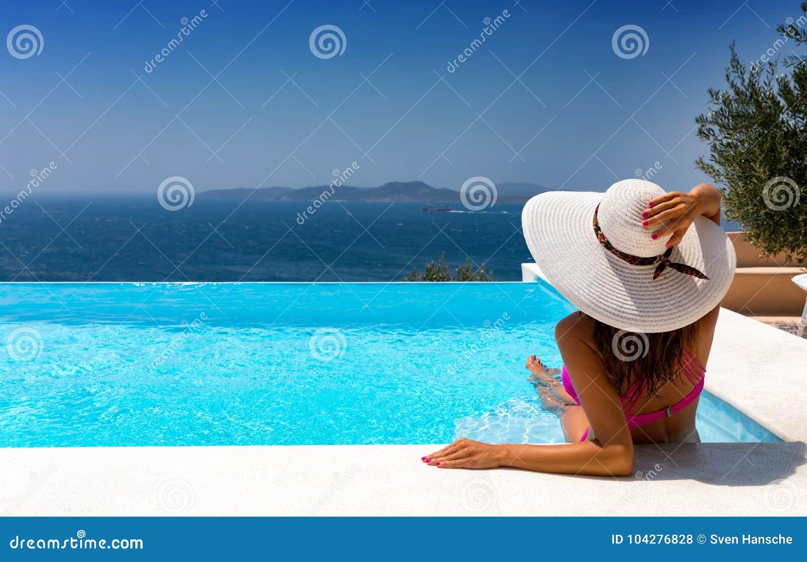 La mujer atractiva es relajante en una piscina del infinito