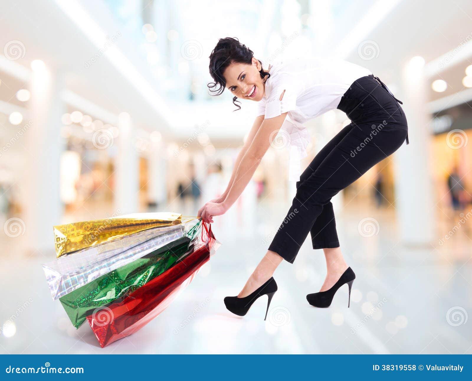 La mujer atractiva feliz arrastra los panieres.