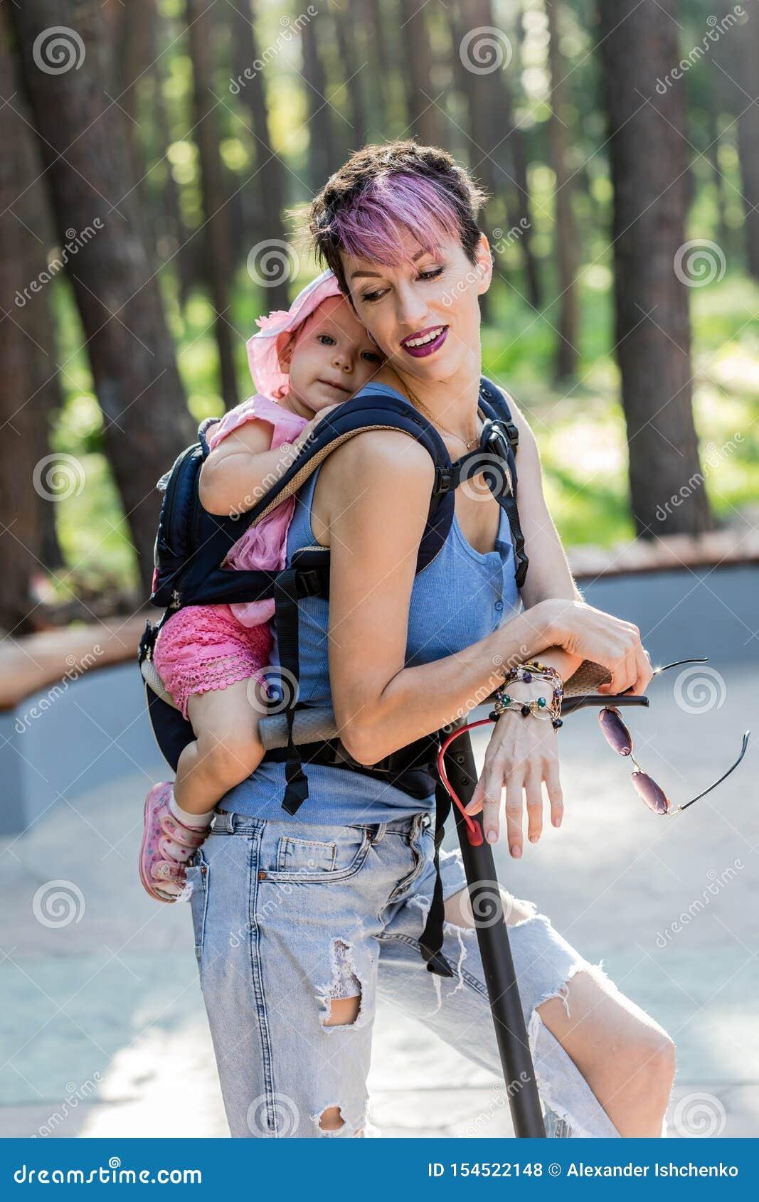 La mujer atractiva fresca goza el montar de una vespa eléctrica con su hija en honda