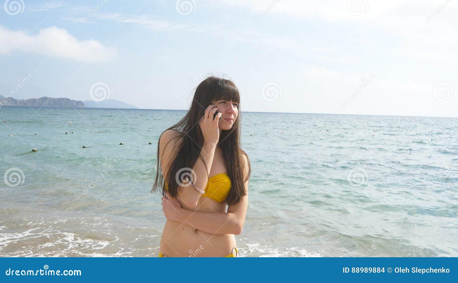 30d17e1db435 La Mujer Atractiva Joven En Un Traje De Baño Está Hablando En El ...