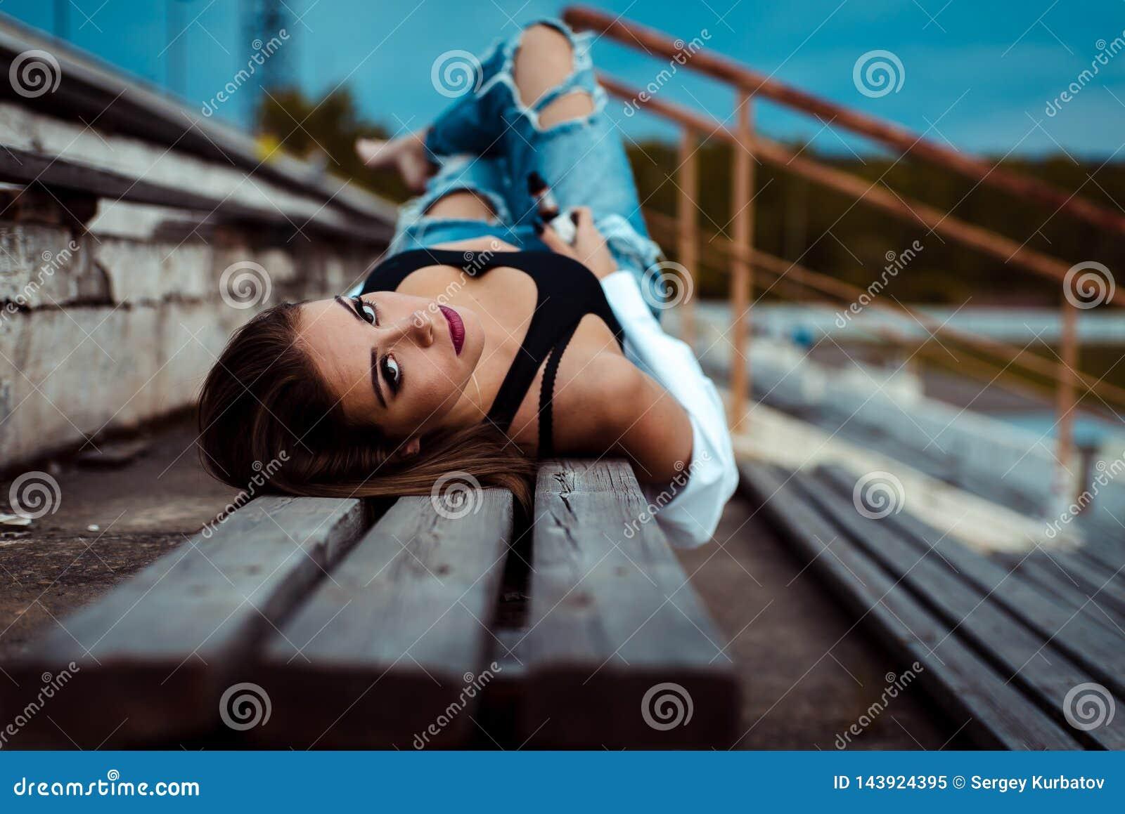 La mujer atractiva joven miente en un banco de madera Ella está tomando la rotura después de entrenamiento en gimnasio outdoor