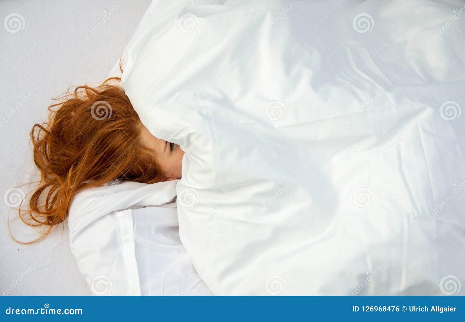 La mujer atractiva, joven, atractiva, pelirroja, hace frente cubierto casi totalmente por las almohadas, un ojo está mirando furt