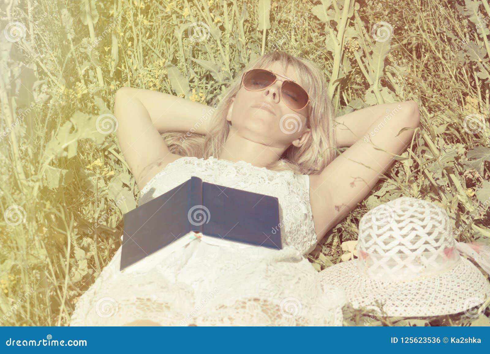 La mujer atractiva miente en el campo y los sueños después de leer el libro