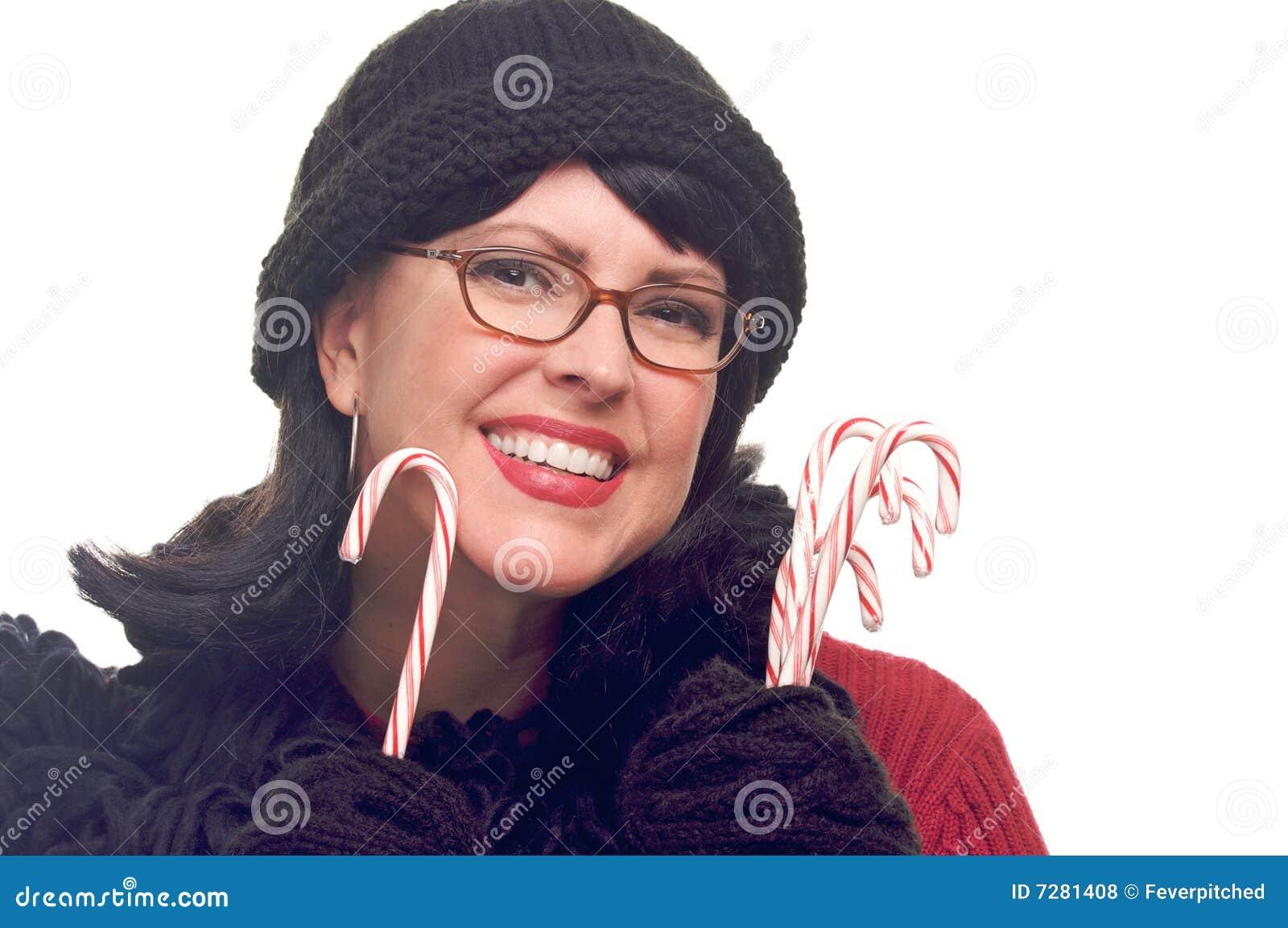 La mujer atractiva sostiene los bastones de caramelo